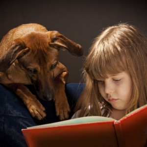 Una bambina legge un libro al suo cane